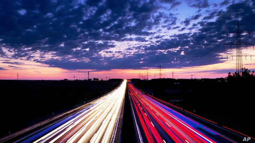Long exposure picture shows driving cars on the highway just before sunrise near Frankfurt, central Germany.