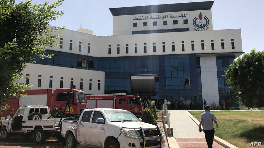 Firefighters and onlookers gather in front of the headquarters of Libya's National Oil Company in the capital Tripoli on September 10, 2018. Armed men stormed the building in Tripoli today where a blast and gunfire were heard, witnesses and a securit