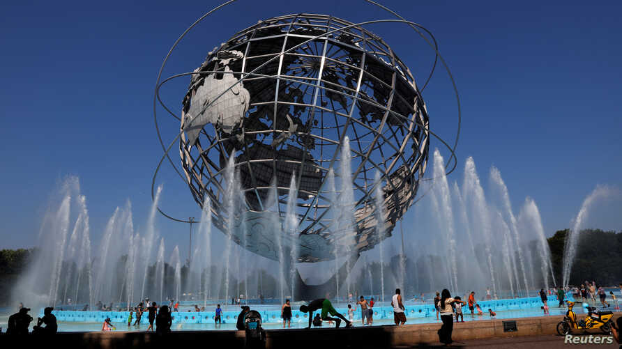 People cool off from the extreme heat from at the Unisphere in Queens, New York, U.S