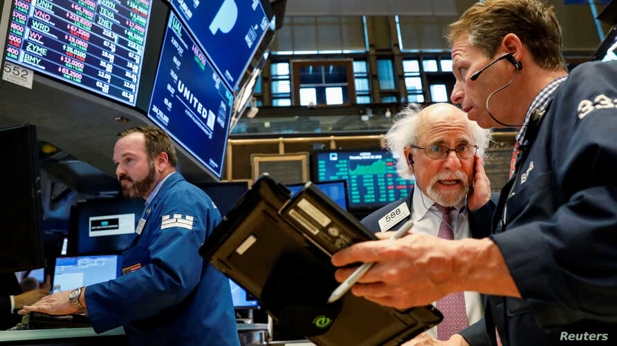 FILE - Traders work on the floor of the New York Stock Exchange (NYSE) in New York, March 29, 2018. With US stocks on a downhill slide, investors worry about President Donald Trump's attacks on giant online retailer Amazon and China's retaliatory imp