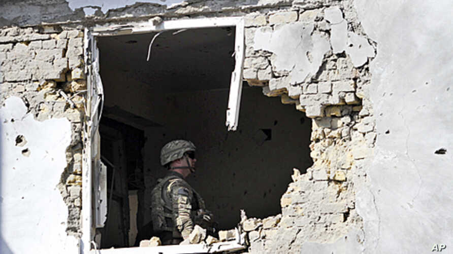 A US soldier checks the damage at offices of the U.N.'s refugee agency, the UNHCR, caused by a suicide bomber, in Kandahar, Afghanistan. A suicide vehicle bomb struck a checkpoint in a neighborhood housing United Nations and international aid groups'