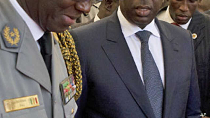 Senegal's newly inaugurated President Macky Sall (R) is surrounded by security as he leaves his swearing-in ceremony at a hotel in Dakar, April 2, 2012