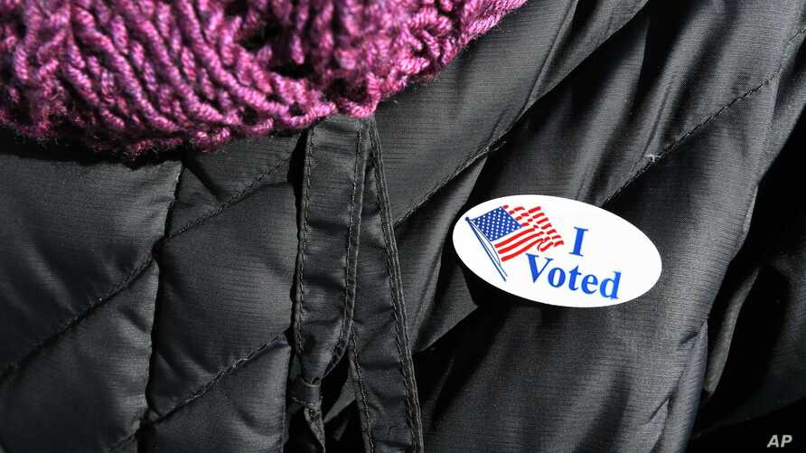 """A woman wears an """"I voted"""" sticker after voting in Massachusetts' primary election in the East Boston neighborhood of Boston, March 1, 2016."""