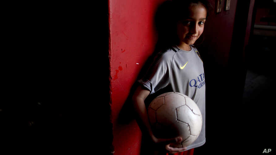 Candelaria Cabrera, 7, poses for a portrait holding a soccer ball in Chabas, Argentina, Sept. 8, 2018. She was 3 years old when her parents gave her her first ball. Her desire to play soccer has called attention to the obstacles women face in the spo