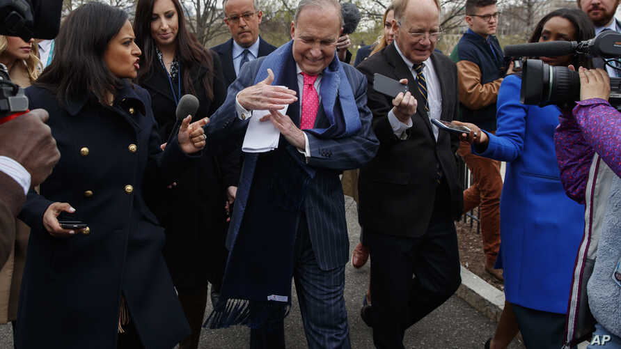 """White House chief economic adviser Larry Kudlow calls for a """"timeout"""" as he talks to reporters outside the White House, April 6, 2018, in Washington."""