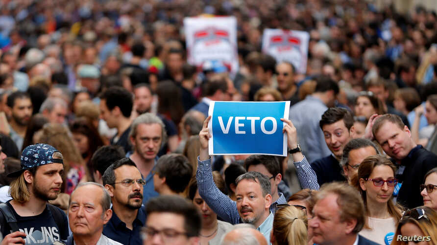 """A demonstrator holds up a banner saying """"Veto"""" during a rally against a new law passed by Hungarian parliament which could force the Soros-founded Central European University out of Hungary, in Budapest, April 4, 2017"""