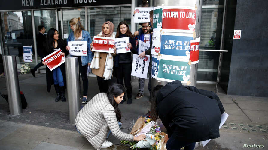 People lay flowers outside New Zealand House, following the Christchurch mosque attack in New Zealand, in London, March 15, 2019.