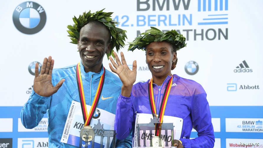 Kenya's Eliud Kipchoge and Gladys Cherono (R) celebrate during the victory ceremony after winning the men's and women's 42nd Berlin marathon, in Berlin, Germany, Sept. 27, 2015.