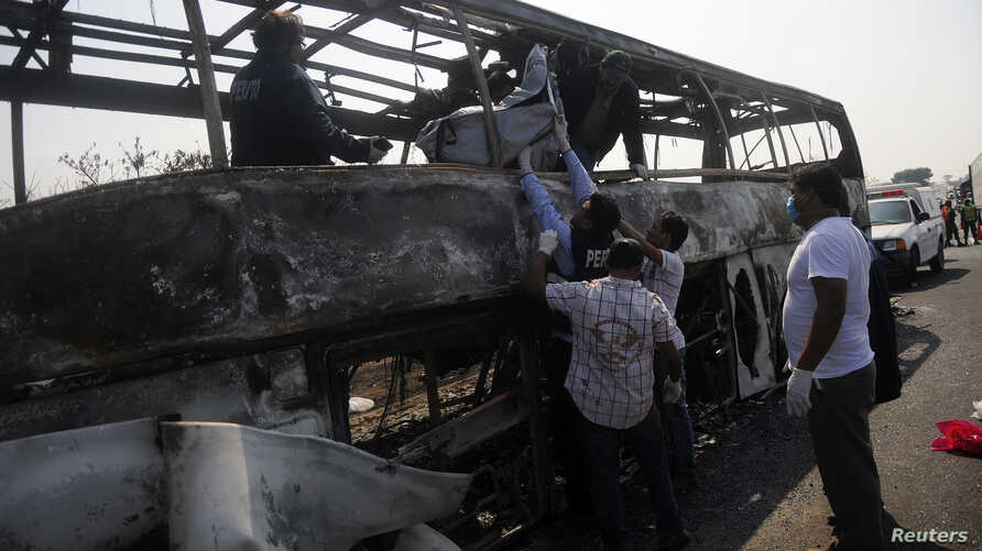Forensic staff pull out a body from a burned bus at the scene of an accident on a highway near Juan Rodriguez Clara town, in Veracruz state, April 13, 2014.