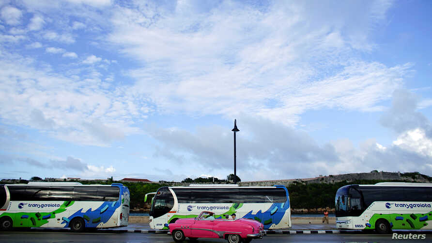 FILE - Tourists ride in a vintage car as they pass by buses owned by the Cuban military-run Gaviota tourism corporation in Havana, Cuba, Nov. 9, 2017.