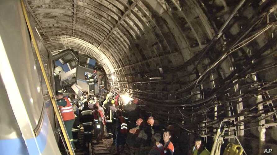 In this frame grab from video provided by the Russian Ministry for Emergency Situations, rescue teams work inside the tunnel in Moscow where a rush-hour subway train derailed Tuesday, July 15, 2014, killing at least 20 people and sending 150 others t...
