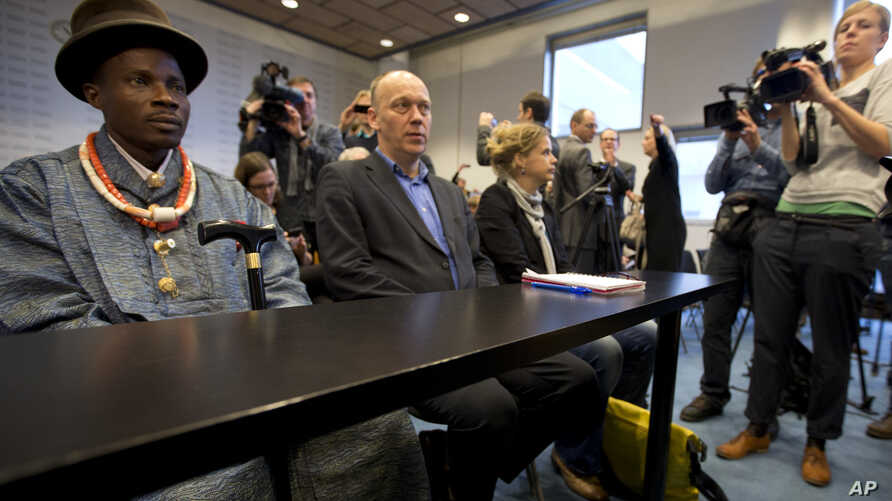 FILE - Friends of the Earth campaign leader Geert Ritsema, second left, and plaintiff Eric Dooh, left, wait for the start of the ruling in the court case of Nigerian farmers against Shell, in The Hague, Netherlands, Jan. 30, 2013.