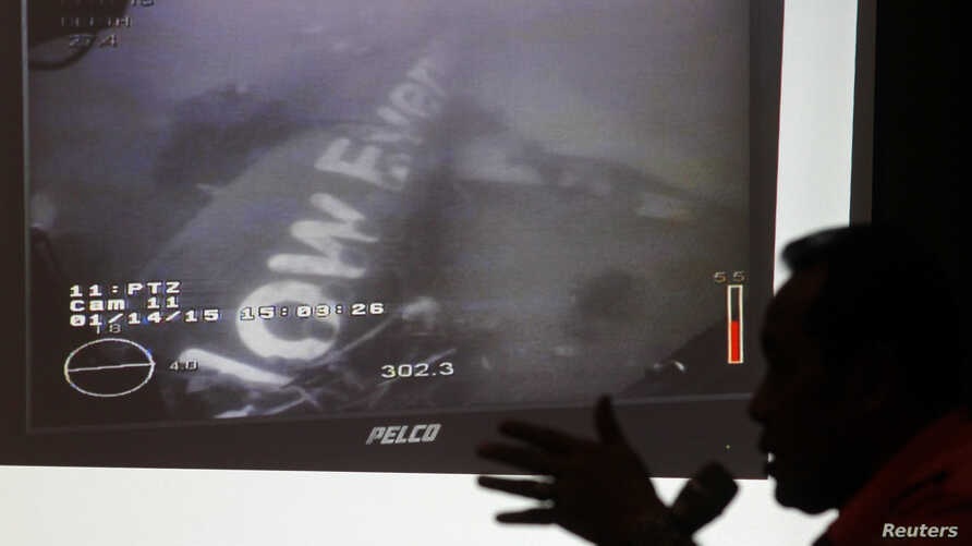 Head of the National Search and Rescue Agency Fransiskus Bambang Soelistyo is seen with an image believed to be of the fuselage of AirAsia Flight QZ8501, taken by an underwater ROV provided by the Singaporean Navy, during a news conference in Jakarta
