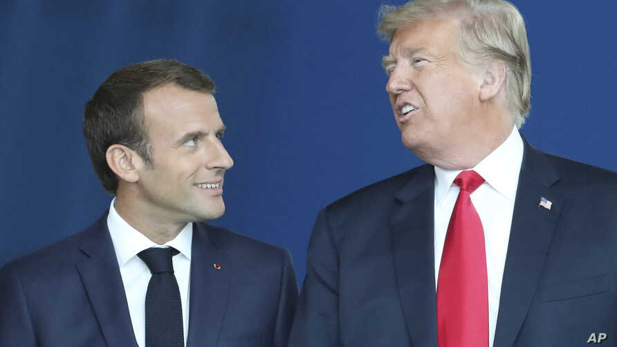 U.S. President Donald Trump speaks with French President Emmanuel Macron as they walk in the atrium during a summit of NATO heads of state and government at NATO headquarters in Brussels, July 11, 2018.