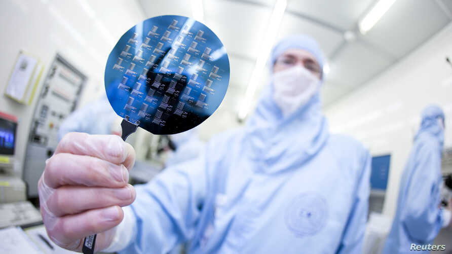 FILE - A scientist presents a silicon wafer.