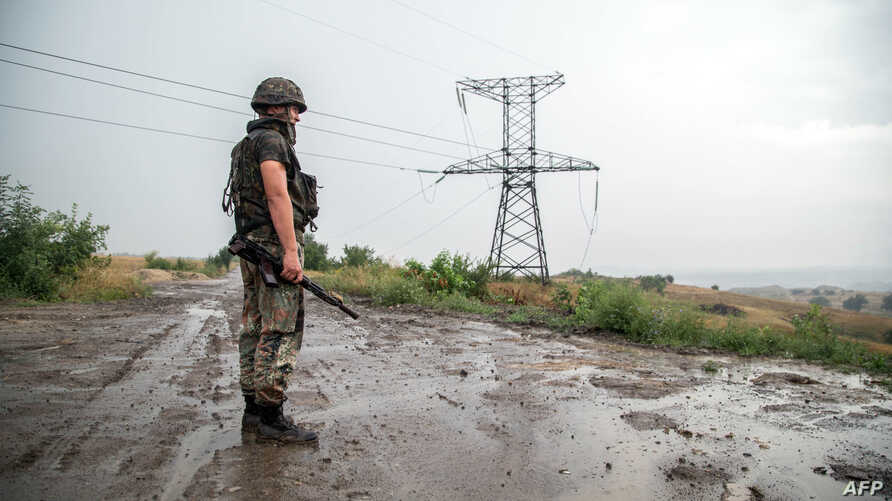 FILE - A Ukrainian serviceman stands near an electricity transmission tower outside the town of Zolote, some 60 km west of Luhansk city, Luhansk region, eastern Ukraine, Aug. 16, 2015.
