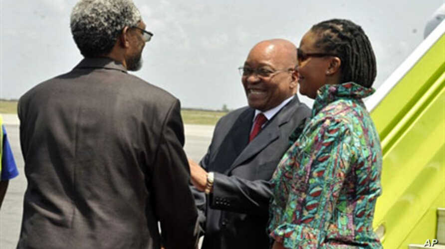 South African president Jacob Zuma (C), flanked by South African ambassador to Ivory Coast Lallie Ntombizodwa (R), shakes hands with African Union representative to Ivory Coast Ambroise Niyonsaba (L) as he arrives at Abidjan international airport on