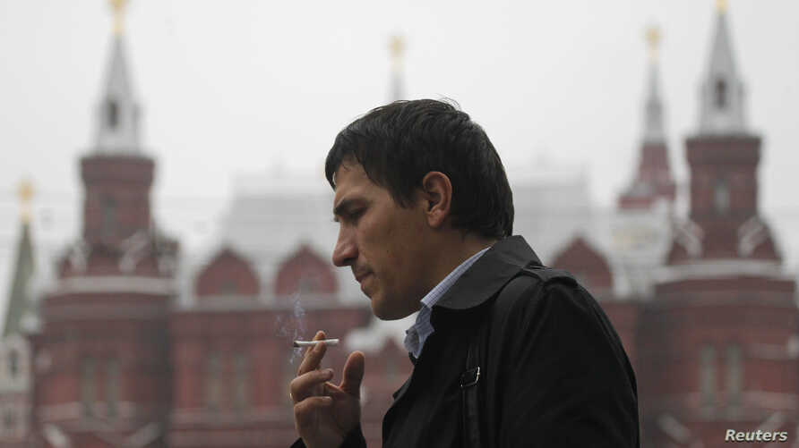 A man smokes along a street in central Moscow October 16, 2012.