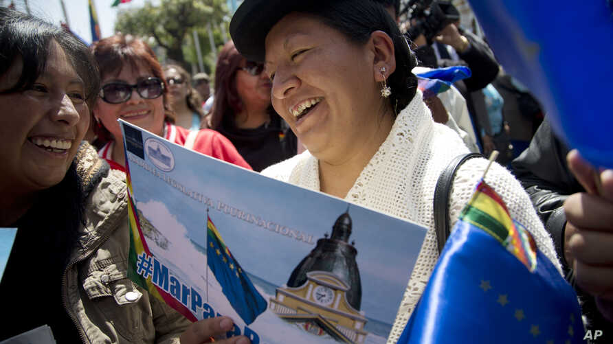 "An Aymara indigenous woman holds a poster that reads in Spanish ""Sea for Bolivia"" during a rally in La Paz in support of Bolivia's bid for access to the Pacific Ocean, Sept. 24, 2015."