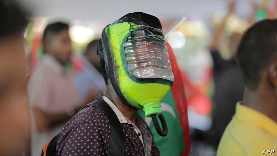 FILE - A protester wears a homemade mask for protection against potential pepper spray or teargas as thousands marched in the capital Male on June 12, 2015.