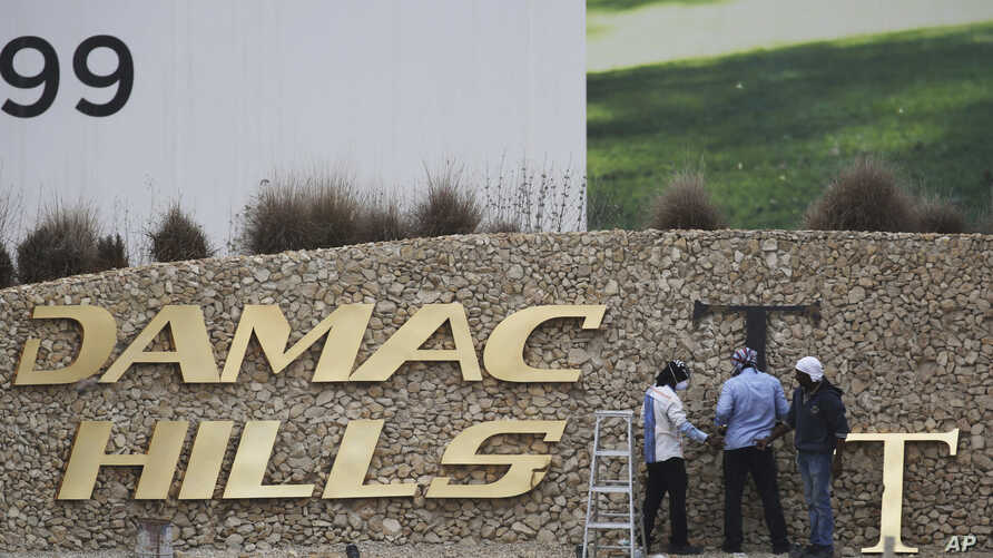 FILE- In this Sunday, Feb. 12, 2017 file photo, workers re-install a gold letter sign for the Trump International Golf Club in Dubai, United Arab Emirates.