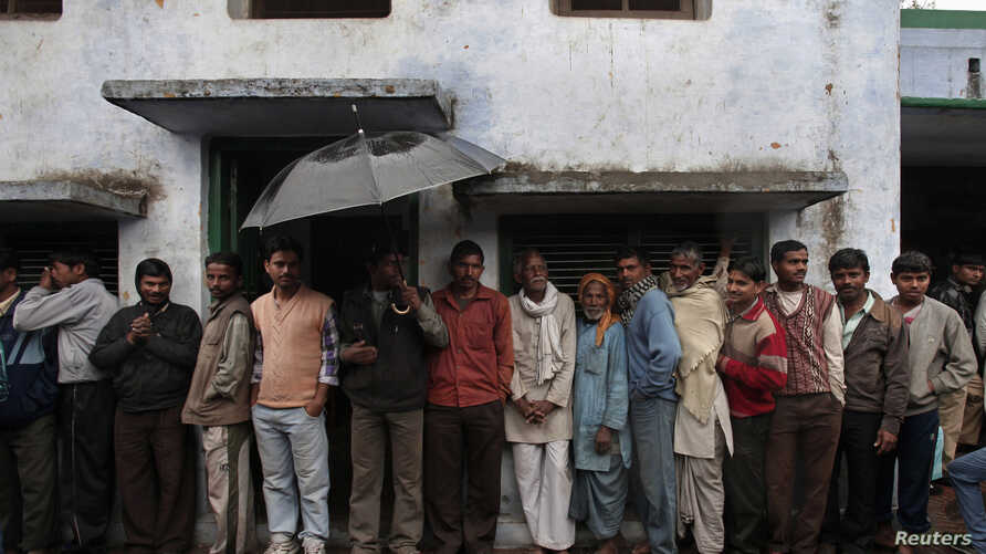 FILE - Voters take shelter from rain as they stand in a queue to cast their ballot at a polling station in Ayodhya during the state assembly election in the northern Indian state of Uttar Pradesh.