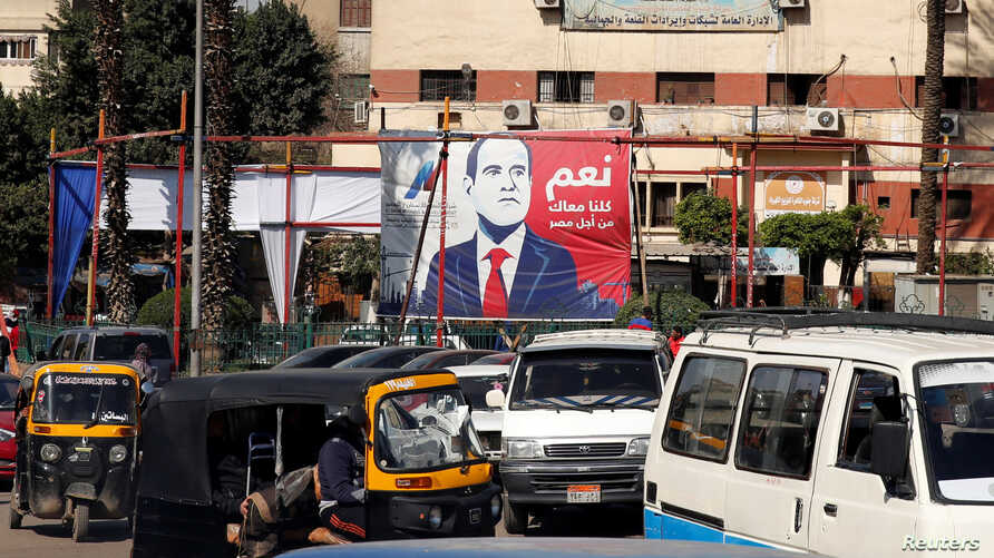 "People and vehicles are seen near a poster of Egypt's President Abdel Fattah al-Sisi for the upcoming presidential election, which reads ""Yes, All of us with you for Egypt"", in Cairo, Feb. 28, 2018."