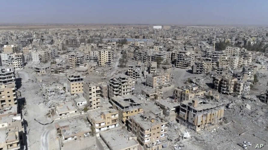 This Thursday, Oct. 19, 2017 frame grab made from drone video shows damaged buildings in Raqqa, Syria two days after Syrian Democratic Forces said that military operations to oust the Islamic State group have ended and that their fighters have taken