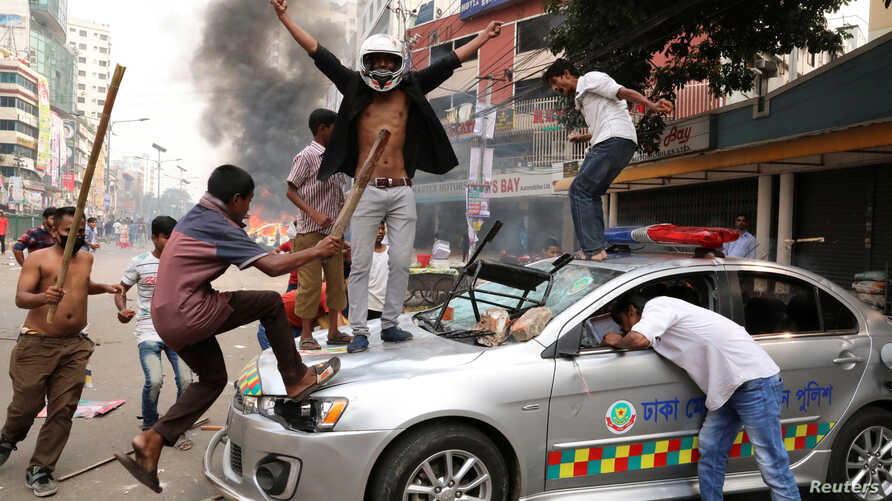 Bangladesh Nationalist Party activists vandalize a police vehicle during clashes in Dhaka, Nov. 14, 2018.