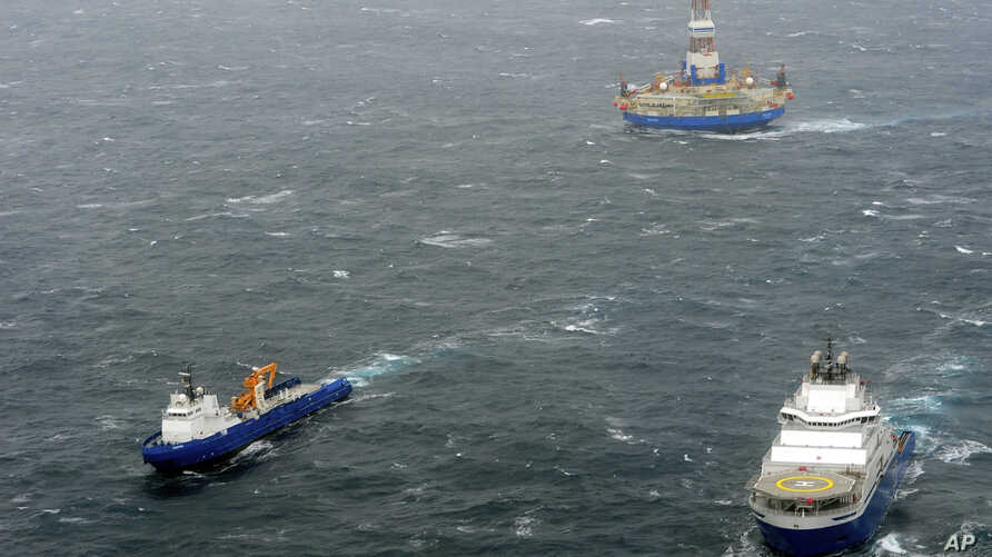 In this photo provided by the United States Coast Guard, the tugs Aiviq and Nanuq tow the mobile drilling unit Kulluk while a Coast Guard helicopter from Air Station Kodiak transports crew members on Saturday, Dec. 29, 2012, 80 miles southwest of Kod...