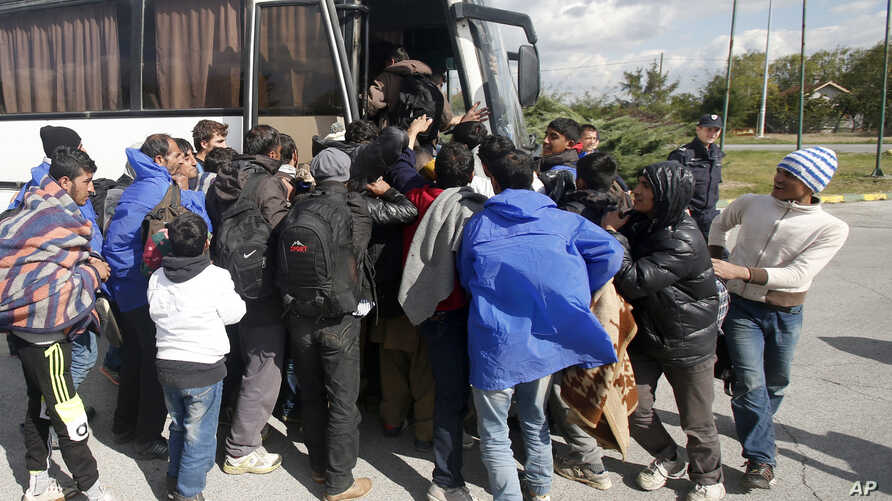 Migrants board a bus at a local gas station near the town of Indjija, about 40 kilometers (24 miles) north of the Belgrade, Oct. 5, 2016.