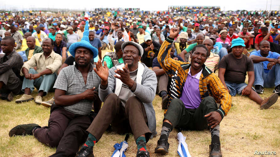FILE - Miners gather at Wonderkop stadium outside the Lonmin mine in Rustenburg, northwest of Johannesburg, Jan. 30, 2014.