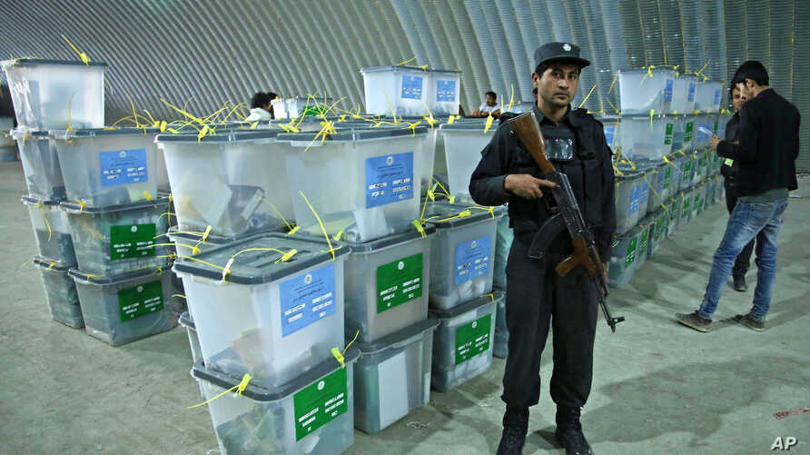 An Afghan police officer stands guard as election workers (R) note serial numbers of ballot boxes at a warehouse of the Independent Elections Commission warehouse in Kabul, April 6, 2014.