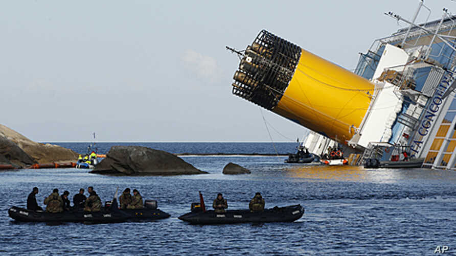 Scuba divers sit in a dinghy next to the Costa Concordia cruise ship which ran aground off the west coast of Italy at Giglio island, January 24, 2012.