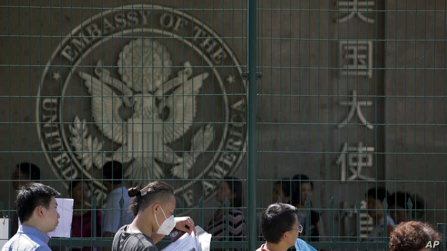 FILE - In this July 26, 2018, photo, visa applicants wait to enter the U.S. Embassy in Beijing, China. The U.S. Homeland Security Department says more than 700,000 foreigners who were supposed to leave the country during a recent 12-month period over