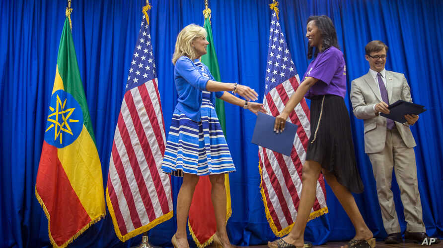 Jill Biden, left, greets a graduate on stage at the Girls Can Code project graduation ceremony at the Colonel John C. Robinson American Center at the National Archive and Library Agency (NALA), in Addis Ababa, Ethiopia, July 17, 2016.