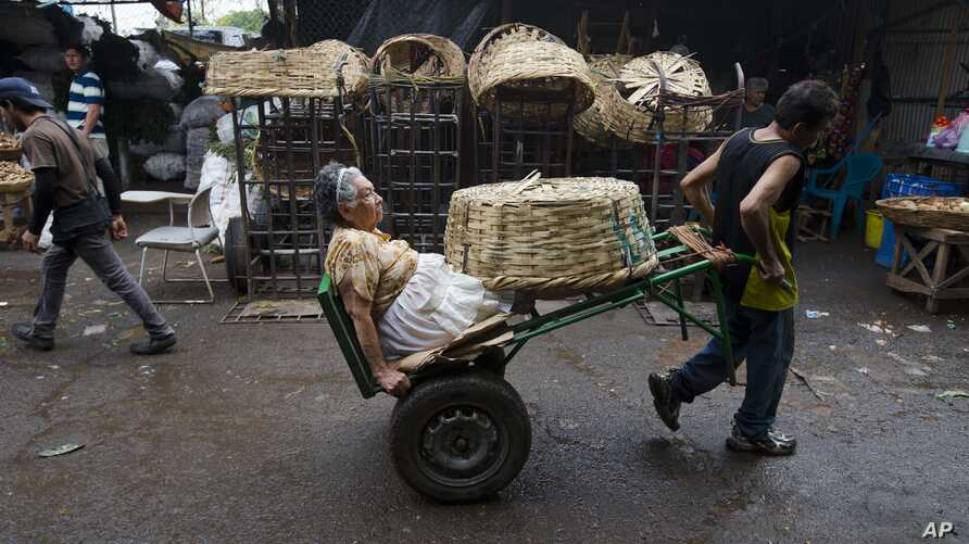 Vendor Carmen Diaz, 84, is pulled by a market porter as she makes her way home at the end of her work day in the Oriental Market in Managua, Nicaragua, April 30, 2015.