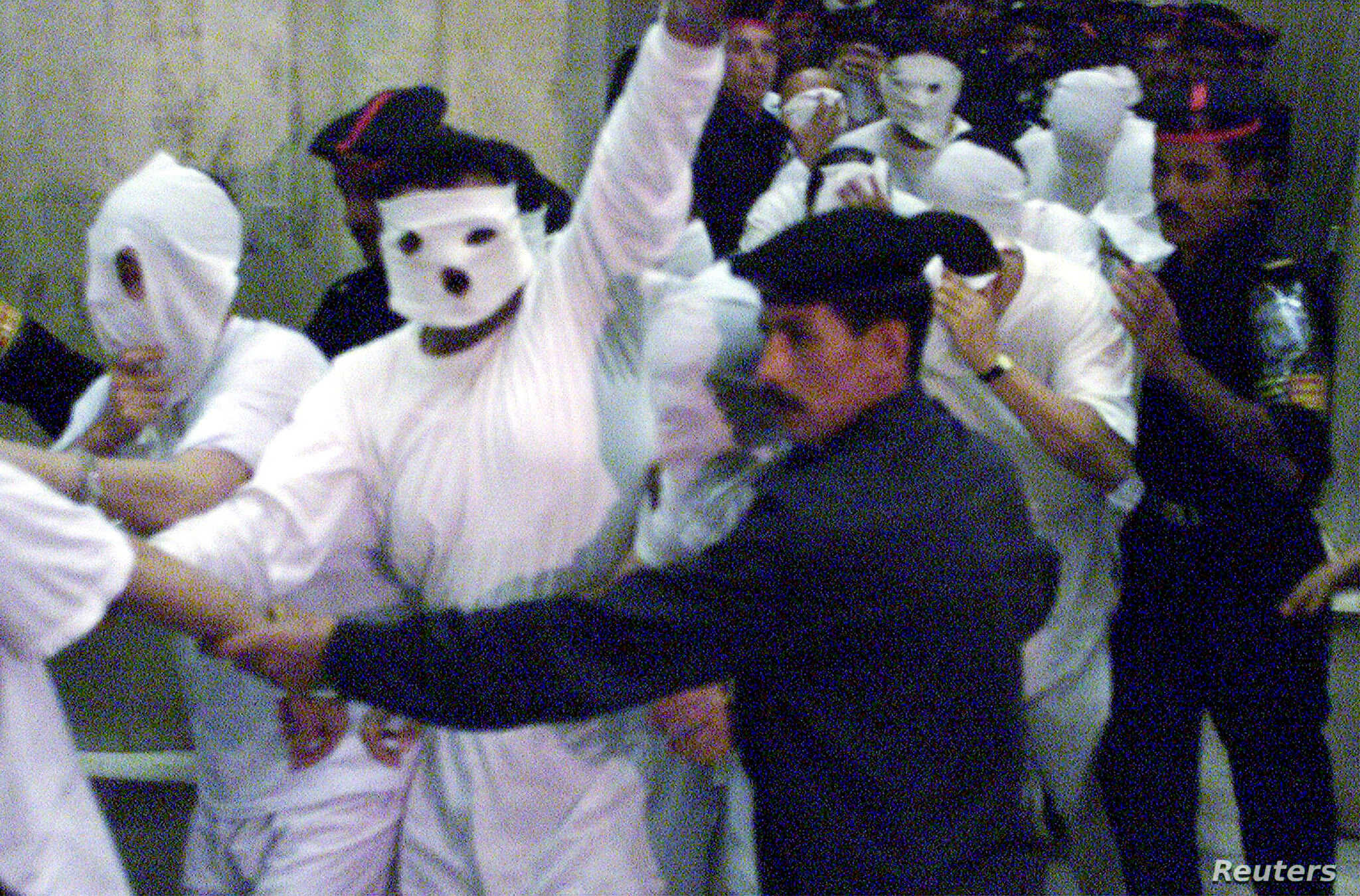 (File Photo) Egyptian security flank 52 suspected homosexual men accused of sexual immorality as they arrive at a Cairo court November 14, 2001.