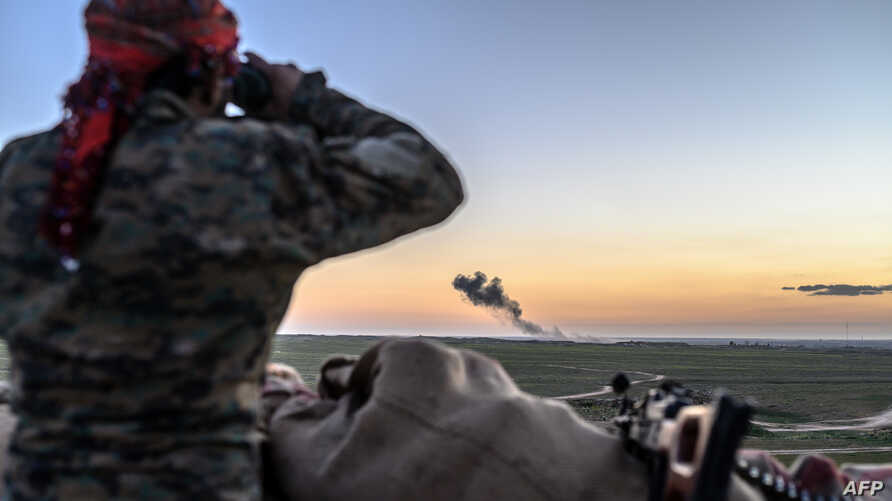A Syrian Democratic Forces (SDF) fighter uses binoculars to inspect the embattled village of Baghuz, Syria, Feb. 19, 2019.