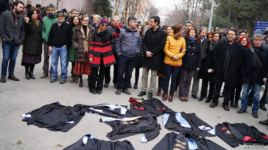 Academics lay down their gowns during a protest against the dismissal of academics from universities following a post-coup emergency decree, in the Cebeci campus of Ankara University in Turkey, Feb. 10, 2017.