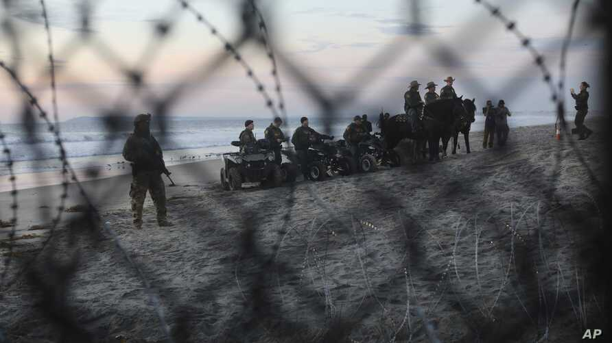 FILE - U.S. Border Patrol agents are seen though the border structure from the Mexican side at a beach in the Pacific Ocean in Tijuana, Mexico, Nov. 16, 2018.