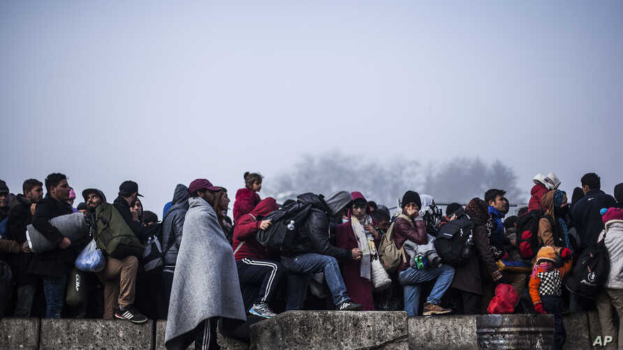 Migrants gather to gain entrance to Austria, at the Slovenian Austrian border, in Sentilj, Slovenia, Nov. 3, 2015. Austria Tuesday proposed a tough new bill to deter Afghans that the U.N. refugee agency criticized as likely to increase the migrants'