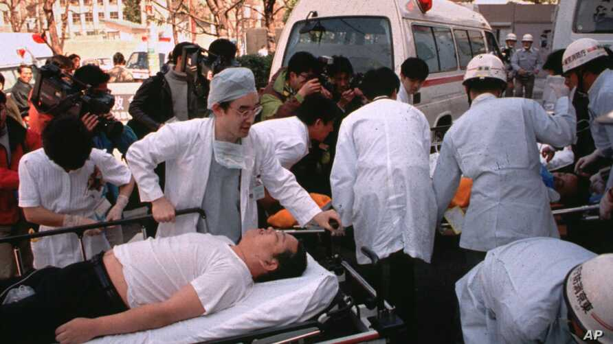FILE - Subway passengers affected by sarin gas planted in the central Tokyo subways by the Aum Shinrikyo doomsday cult are carried into St. Luke's International Hospital in Tokyo, March 20, 1995.