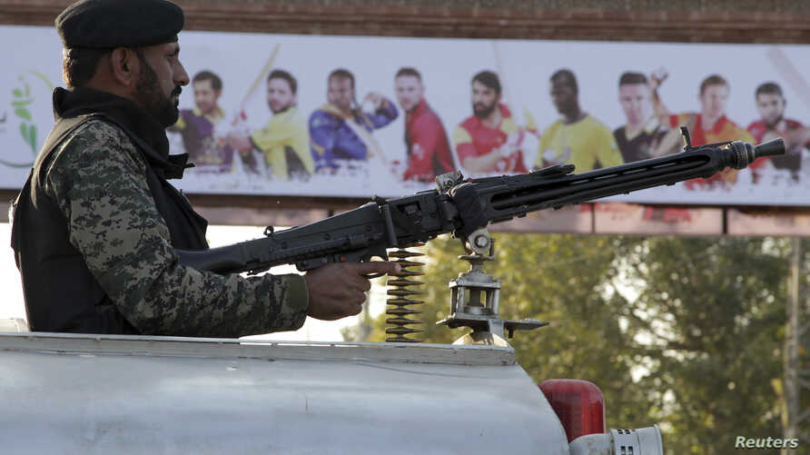 A Pakistani paramilitary soldier monitors the area near an entry gate of Gaddafi stadium for the final cricket match of Pakistan Super League, in Lahore, Pakistan, Saturday, March 4, 2017.