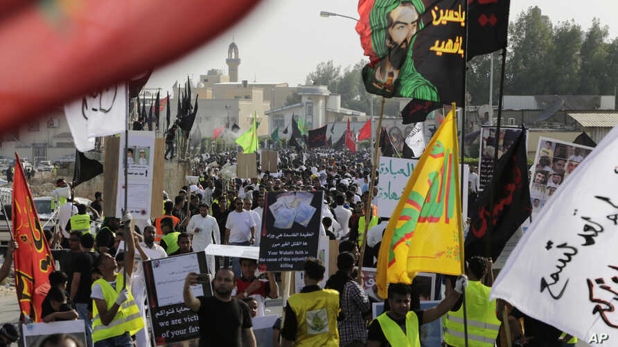 Saudis marching in a funeral procession carry religious flags and signs in English and Arabic blaming the fundamentalist Wahhabi stream of Sunni Islam's ideology for recent suicide attacks on Shiite mosques in the kingdom, May 30, 2015, in Tarut, Sau