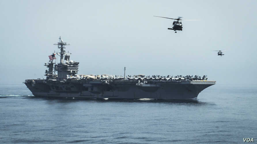 Helicopters fly from the aircraft carrier USS Theodore Roosevelt (CVN 71) during a vertical replenishment with the aircraft carrier USS Carl Vinson (CVN 70), Apr 13, 2015.