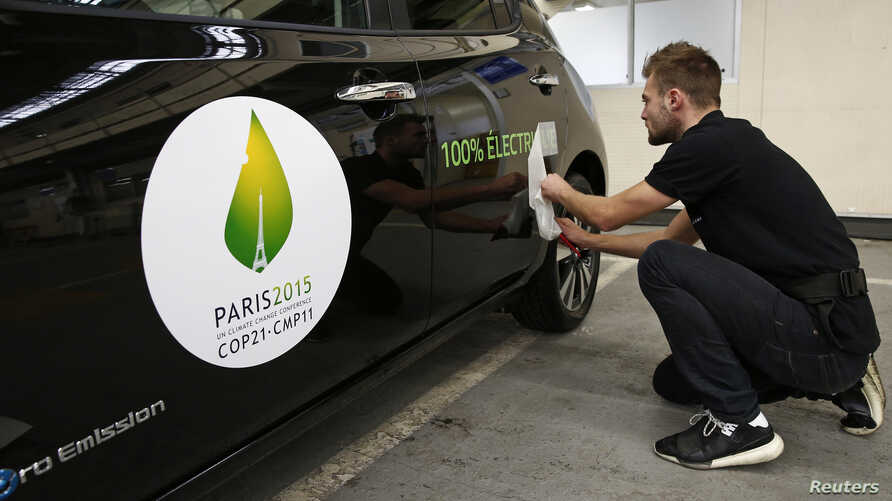 FILE - An employee installs a sticker which reads 100% electric next to the logo of the upcoming COP21 Climate Change Conference on a Nissan LEAF electric car in Boulogne-Billancourt, near Paris, France, November 16, 2015.