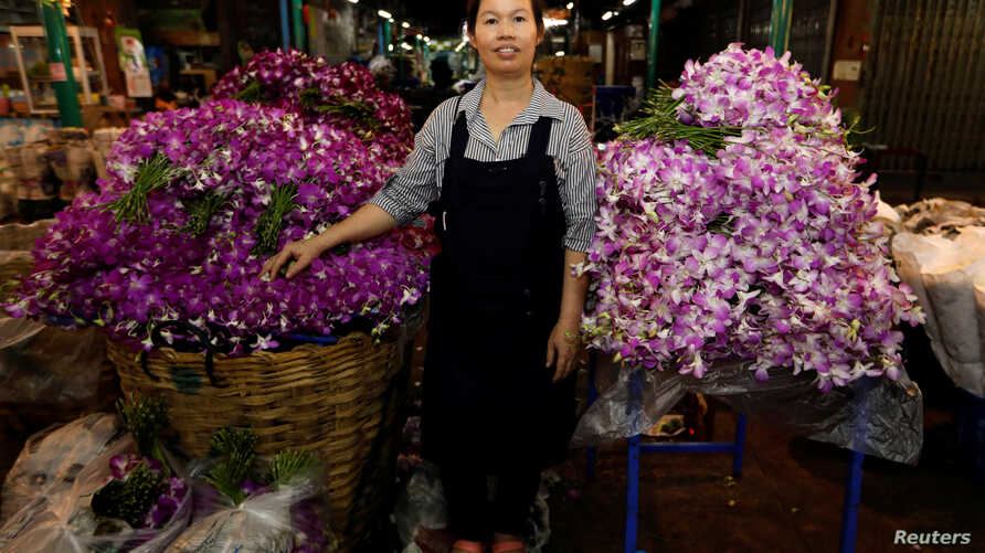 Ram, 46, poses for a photograph at her stall at the flower market in Bangkok, Thailand, Feb. 26, 2017.