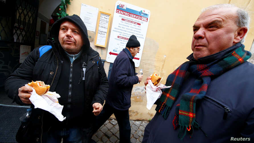 Needy people eat cheeseburgers donated by McDonald's to a charity organization which bestowed them at a walk-in clinic in Rome, Italy, Jan. 16, 2017.