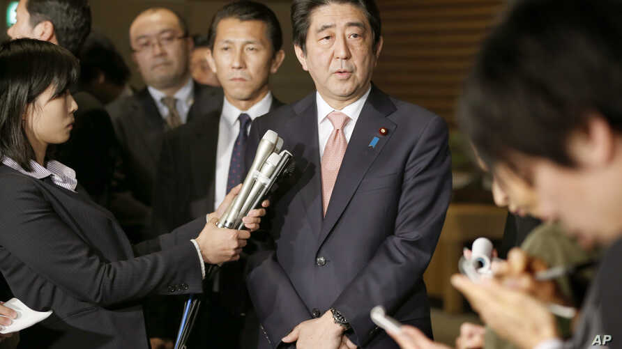 Japan's Prime Minister Shinzo Abe, center, speaks to reporters at the prime minister's official residence in Tokyo, Wednesday, Jan. 21, 2015.